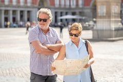 Senior couple lost using city map for finding their location in Europe. Senior tourist couple lost having an argument while using a map in plaza Mayor madrid stock photos