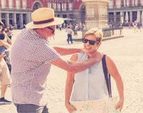 Senior couple lost using city map for finding their location in Europe. Senior tourist couple lost having an argument while using a map in plaza Mayor madrid royalty free stock image