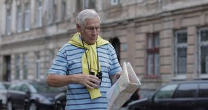 Senior tourist exploring town with a map. Looking in binoculars. Senior male tourist exploring town with a map in hands and looking for the route while traveling stock video