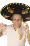 Senior tourist male Mexican somebrero hat. Middle age senior tourist male wearing Mexican sombrero Mariachi hat drinking tequila shot with slice of lemon Stock Photos