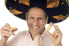 Senior tourist male Mexican somebrero hat dri. Middle age senior tourist male wearing Mexican sombrero Mariachi hat drinking tequila shot with slice of lemon Royalty Free Stock Images