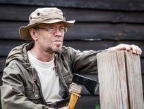 Senior tourist man with axe. Outdoor Royalty Free Stock Photo