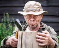 Senior tourist man with axe. Outdoor Royalty Free Stock Photography