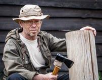 Senior tourist man with axe. Outdoor Stock Photo