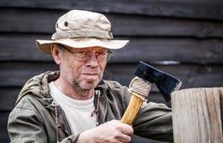 Senior tourist man with axe. Outdoor Stock Image
