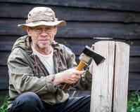Senior tourist man with axe. Outdoor Royalty Free Stock Image