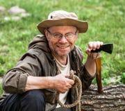 Senior tourist man with axe Stock Images