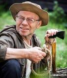 Senior tourist man with axe Royalty Free Stock Photo