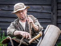 Senior tourist man with axe. And rope outdoor Stock Image