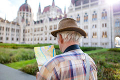 Senior tourist man in hat searching for destination on map. At Hungarian Parliament, Budapest, Hungary Stock Images