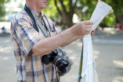 Senior tourist man with map and camera in public park Royalty Free Stock Image