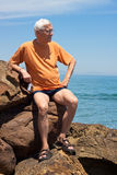 Senior tourist man on the rocky beach. Portrait of senior tourist man sitting on the rocky beach in Spain Royalty Free Stock Photography