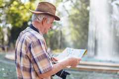 Senior tourist man searching for destination on map Royalty Free Stock Image