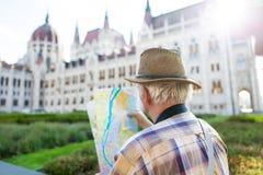 Senior tourist man watching map at Parliament, Budapest, Hungary Stock Image