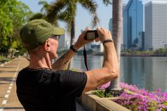 Senior tourist man wearing cap while taking pictures at peaceful. Park in Bangkok Thailand stock images