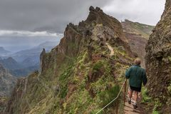 Trail on the ridge Madeira. Senior tourist in the mountains of Madeira at Pico do Areeiro Arieiro, while hiking to Pico Ruivo on a cloudy summer day with ominous stock image
