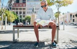 Senior tourist reading a city map Stock Images