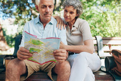 Senior tourist sitting on a park bench with a city map. Senior tourist sitting on a park bench reading city map. Man and women using city guide for finding their Royalty Free Stock Photography