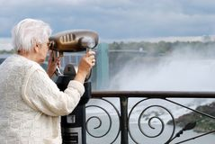 Senior tourist using binoculars at niagara falls. Closeup of a senior woman tourist using binoculars at niagara falls stock photos