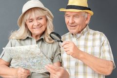 Senior tourists in beach hats studio standing isolated on gray holding magnifier looking at map happy close-up royalty free stock photo
