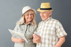 Senior tourists in beach hats studio standing on gray with map woman showing husband pictures on smartphone royalty free stock image