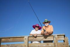 Senior Tourists Fishing. Happy senior couple has fun fishing on their Florida vacation royalty free stock photography
