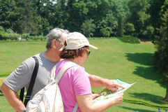Senior tourists with map. Senior couple on the vacation reading a map Royalty Free Stock Image