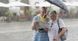 Senior tourists in rainy weather stand and looking for the route in map. Happy two senior tourists in rainy weather stand downtown and looking for the route in stock video