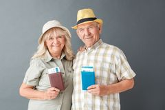 Senior tourists studio standing isolated on gray holding passports and tickets looking camera happy stock images