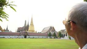 Senior travel toWat Phra Kaew, Grand palace, Temple of the Emerald Buddha with sky and green lawn. Landmark of Bangkok Thailand stock video