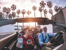 Senior trendy couple inside a convertible car on holiday time - Mature people having fun doing a road trip during vacation -