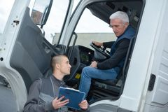 Senior truck driver taking to manager. Lorry royalty free stock images