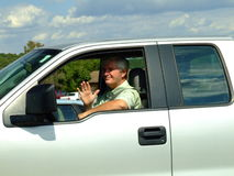 Senior in Truck Waving to You. Baby-boomer man smiling and waving out of the window of his truck Stock Photo