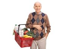 Senior trzyma kosz sklepy spożywczy pełno Fotografia Royalty Free