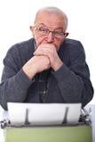 Senior and typewriter. Portrait of senior man with aged typewriter isolated on white Royalty Free Stock Photo