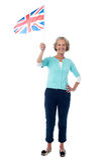 Senior UK supporter waving national flag. Senior woman holding UK flag, full length portrait Royalty Free Stock Image