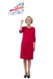 Senior UK supporter waving national flag. Senior woman holding UK flag, full length portrait Stock Photography