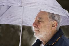 Senior under umbrella. Senior with grey hair holding an umbrella under icy rain Stock Photography