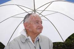 Senior under an umbrella Stock Image