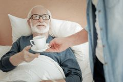 Senior unshaken man lying and taking a cup. I need care. Senior unshaken bespectacled men lying on the bed looking up and taking a cup Stock Image