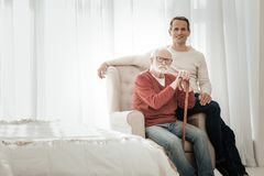 Senior unshaken man sitting on the chair and looking straight. Together is better. Senior unshaken bespectacled men spending time with his son sitting on the Stock Image
