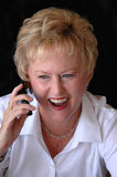 Senior using cell phone. An older business woman on a cell phone laughing Stock Photo