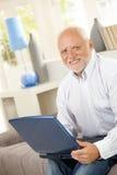 Senior using laptop computer on sofa Royalty Free Stock Image