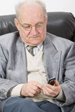 Senior using a mobile phone. Close-up image of a senior man typing a message on his mobile phone Royalty Free Stock Image