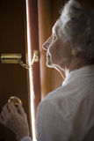 Senior using a security chain. Senior woman using a security chain on front door Stock Photo