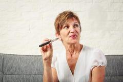 Senior Vaping, Enjoying An Electronic Cigarette. Senior woman vaping, enjoying an electronic cigarette royalty free stock images
