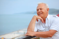 Senior on veranda, lean elbows about handrail Royalty Free Stock Photography