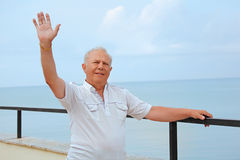 Senior on veranda, lifted hand upwards Royalty Free Stock Images