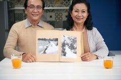 Showing wedding photos. Senior Vietnamese couple showing album with their black and white wedding photos stock photo