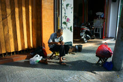 Senior Vietnamese man, repair shoes Stock Photo